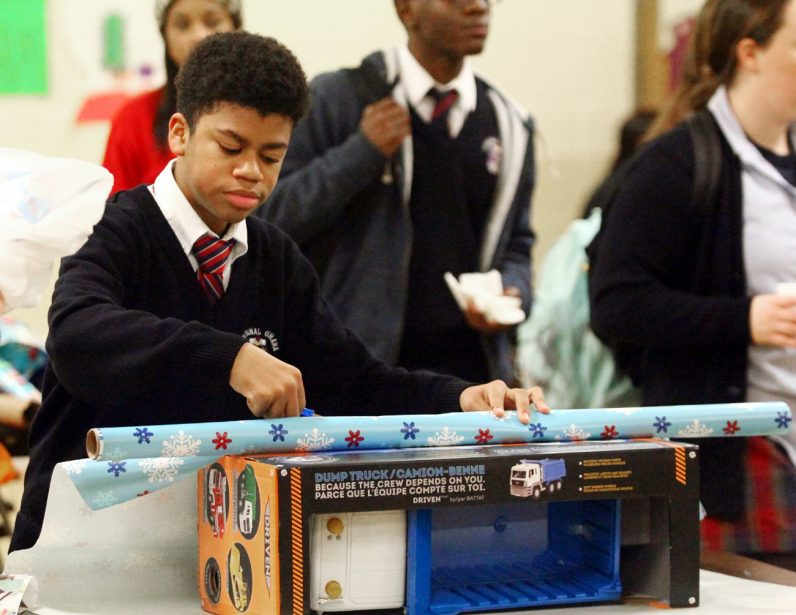 Freshman Brandon Baskerville wraps a toy truck he purchased for a child in need.