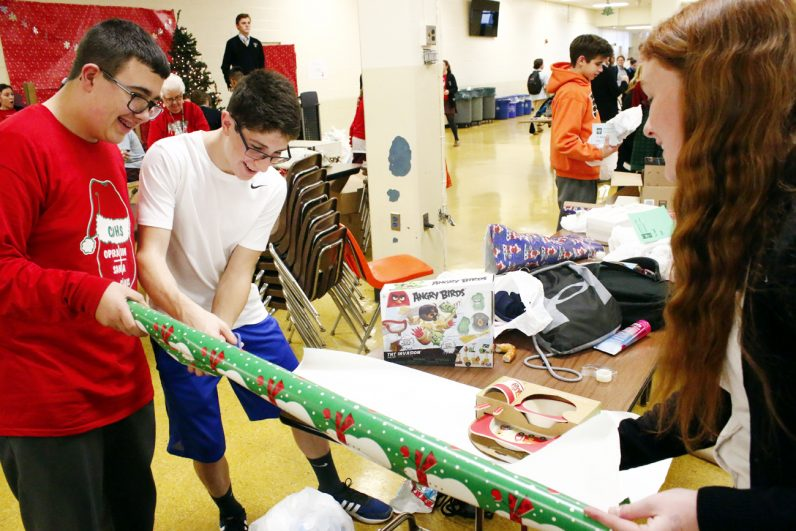 Tyler Lesage, Angelo Brunetti and Kelly Cook use team work to get a present wrapped.
