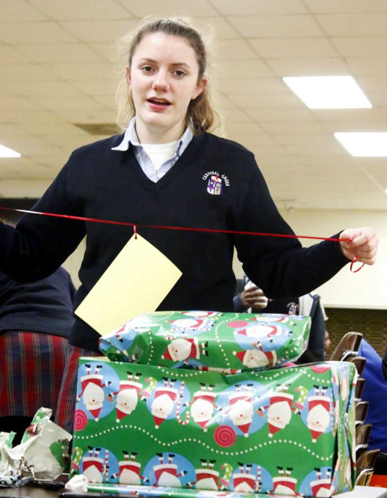 Junior Emma Knaub tags and ties the presents she wrapped.