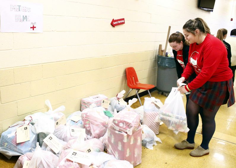 Seniors Meghan MacWilliams and Catharine Ward organize one of the piles of toys that were wrapped at Cardinal O'Hara High School on Dec. 13.