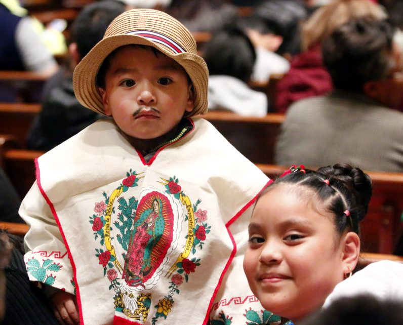 Jayden Medina, dressed as St. Juan Diego to whom the Blessed Virgin Mary appeared in 1531 in Mexico, and his aunt Marleny Nava attend Mass at the cathedral honoring Our Lady of Guadalupe.