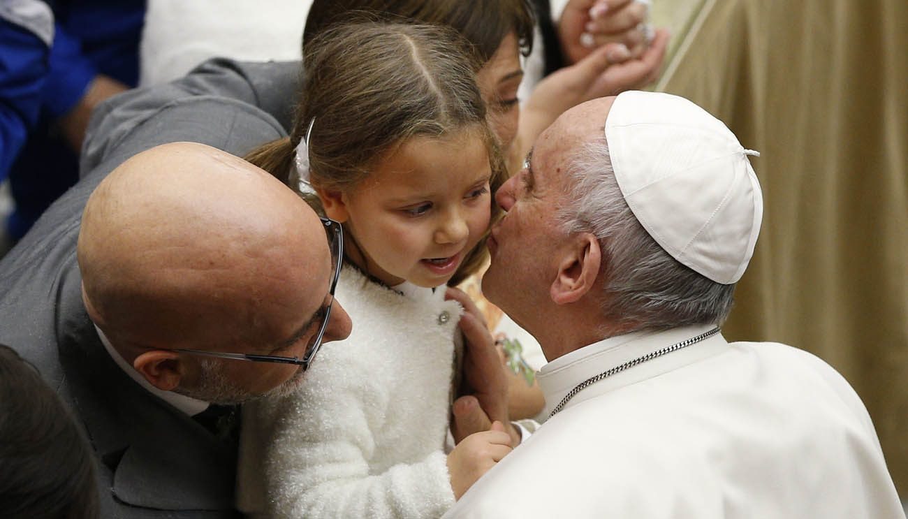 Pope Francis kisses a young girl during his general audience in Paul VI hall at the Vatican Dec. 14. (CNS photo/Paul Haring)