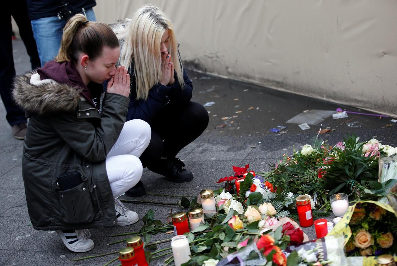 Women pray in front of a makeshift memorial Dec. 20 at the scene where a truck plowed into a crowded Christmas market the previous day in Berlin. The terrorist attack killed at least a dozen people and injured nearly 50 as it smashed through tables and wooden stands. (CNS photo/Fabrizio Bensch, Reuters)