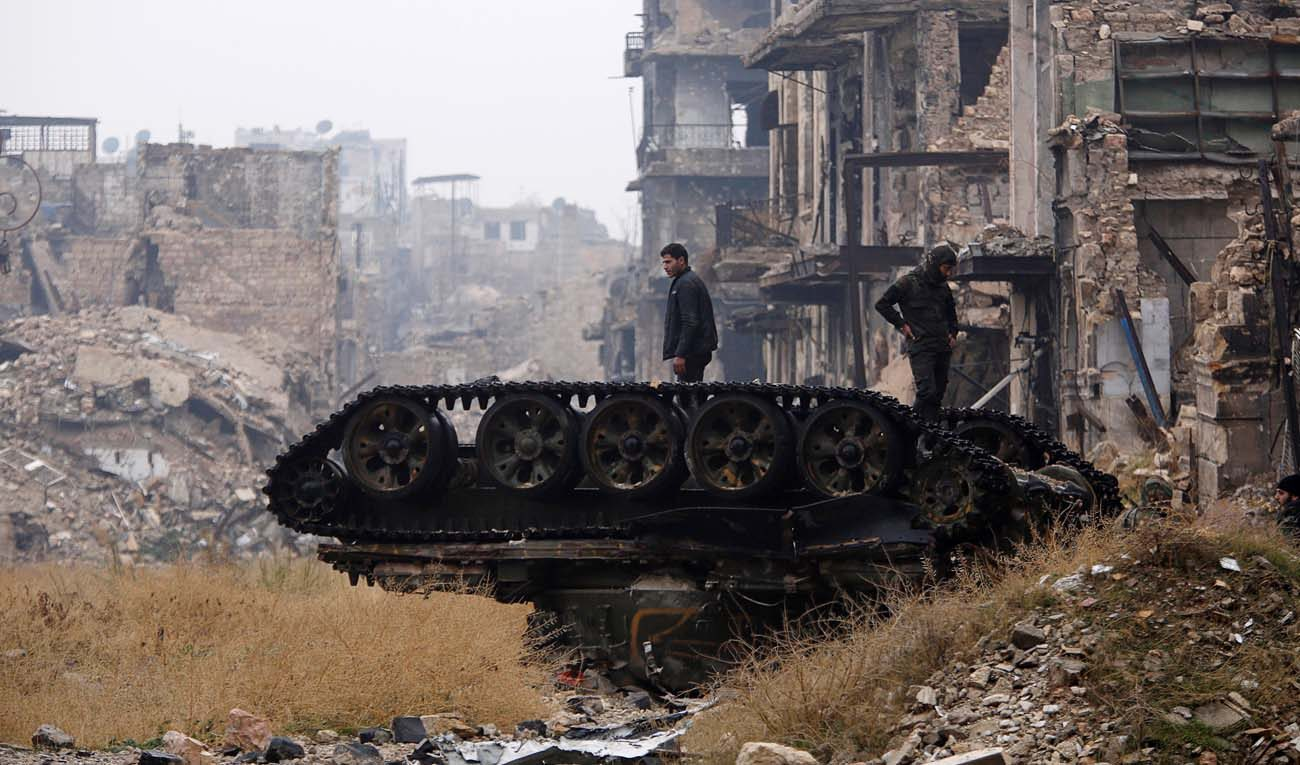Forces loyal to  Syrian President Bashar Assad stand atop a damaged tank Dec. 13  in the destroyed government-controlled area of Aleppo. Rejecting violence as a way to solve problems is not a sign of weakness, but rather requires courage and honesty, Pope Francis told diplomats. (CNS photo/Omar Sanadiki, Reuters)