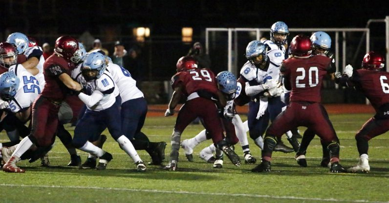 The Hawks prevent North Penn's Ricky Johns from gaining yards on a crucial fourth-and-one play in the fourth quarter.