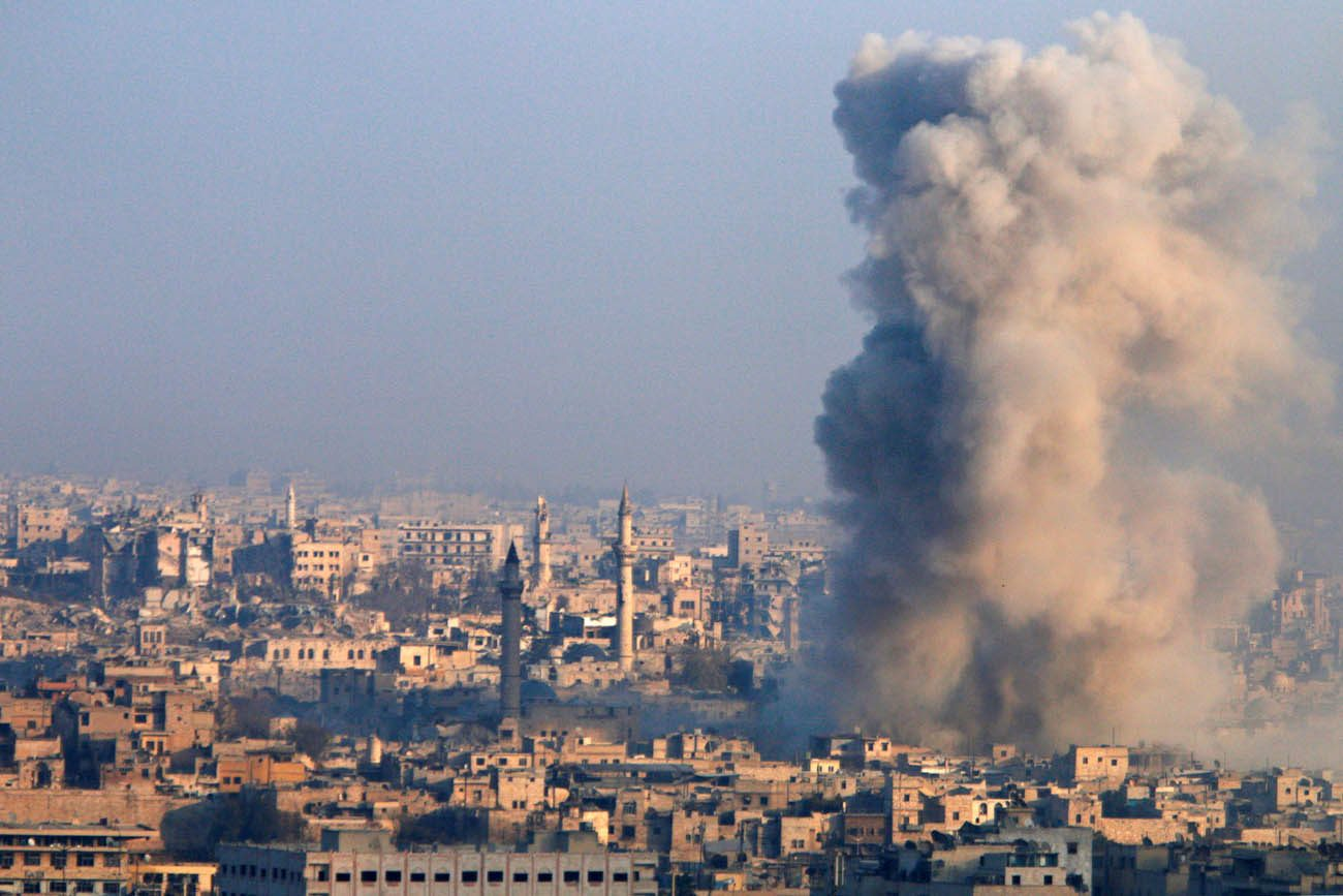 Smoke rises from a government-held area of Aleppo, Syria, after a Dec. 12 explosion. (CNS photo/Omar Sanadiki, Reuters)