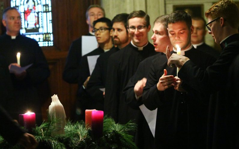 Seminarians light candles from the Advent wreath before processing into St. Martin's Chapel.