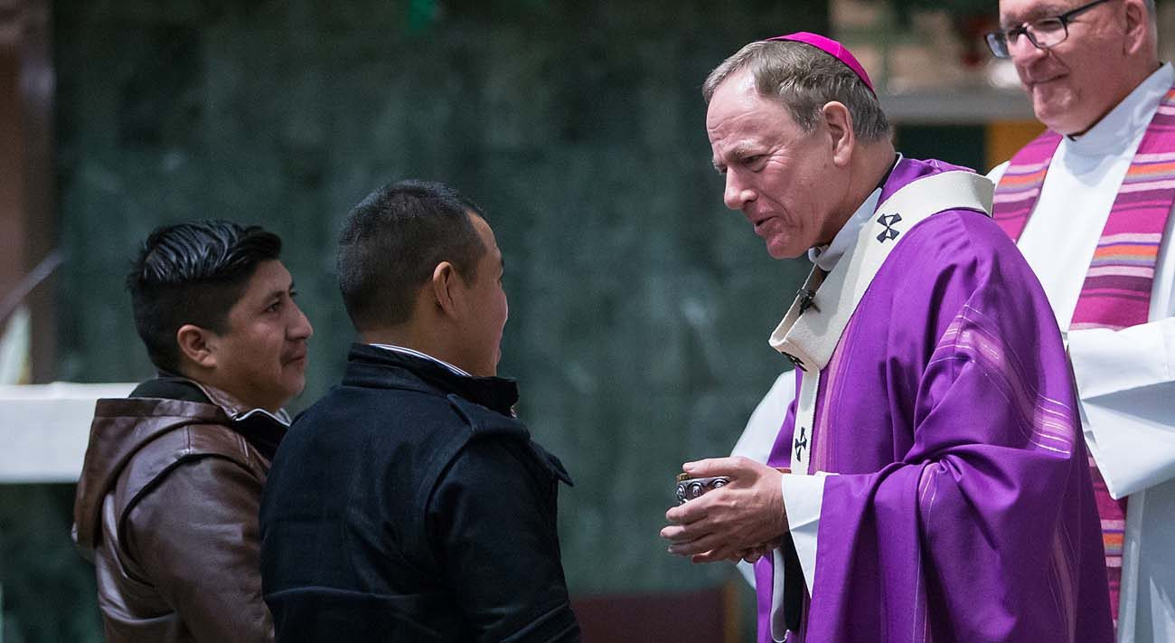Archbishop Michael Miller of Vancouver, British Columbia, receives the gifts during a Dec. 17 Mass for migrant workers at Our Lady of Sorrows Church in Vancouver. (CNS photo/Ben Nelms)