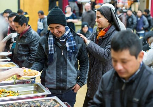 A nun shares a light moment with a man during a meal following a Dec. 17 Mass for migrant workers at Our Lady of Sorrows Church in Vancouver, British Columbia. (CNS photo/Ben Nelms)