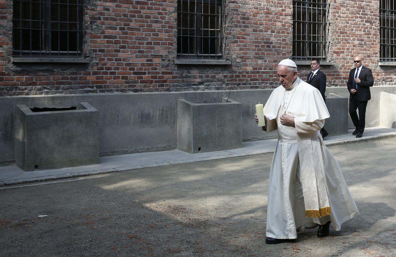 Pope Francis carries a candle as he visits the Auschwitz Nazi death camp in Oswiecim, Poland, July 29. The pope visited the camp while attending World Youth Day. (CNS photo/Paul Haring)