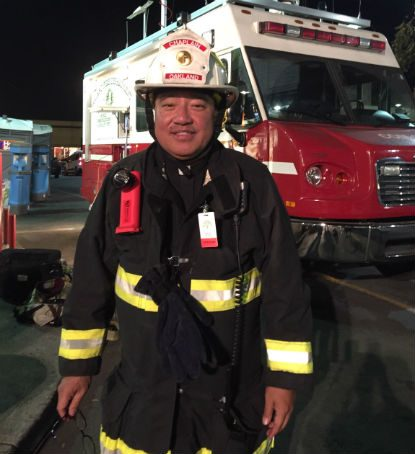 Father Jayson Landeza, pastor of St. Benedict Parish in Oakland, Calif., and chaplain to the Oakland Police and Fire departments, is seen Dec. 5 near the site of the Oakland warehouse fire. Father Landeza assisted family members of victims of the Dec. 2 warehouse fire, which killed 36. (CNS photo/courtesy Father Landeza)