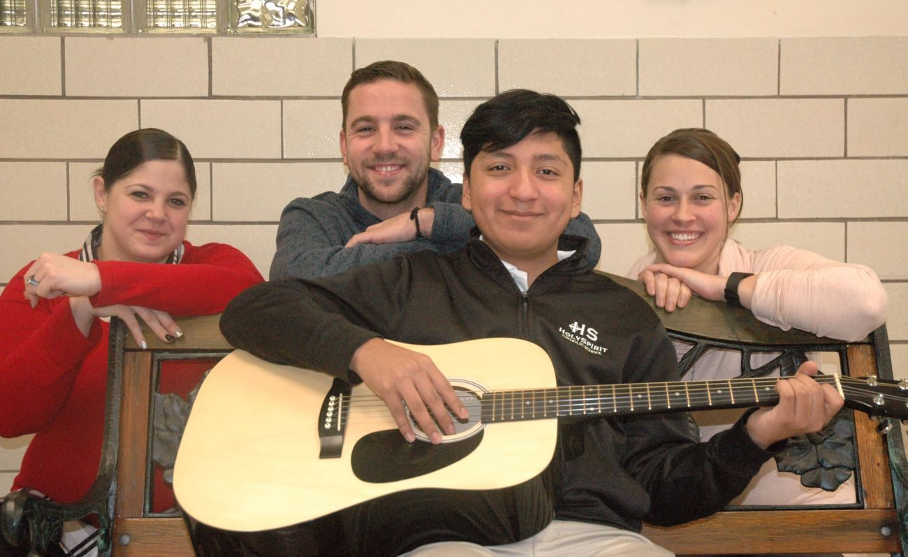 Ethan Velazquez, a 12-year-old at Holy Spirit School in Indianapolis, plays his guitar alongside school staff members Stacy Inman-Davidson, Lucas Stippler and Lauren McLaughlin. The three staffers are credited with their quick actions to help save the life of Ethan, who had a heart attack on the school playground in May 2016. (CNS photo/John Shaughnessy, The Criterion) .