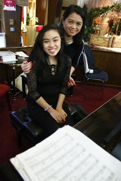 God, family and music are the priorities for Anna Alquiros (center), to which she devotes herself along with her mother, Angela, at Epiphany of Our Lord Church and at Archbishop John Carroll High School. (Sarah Webb)