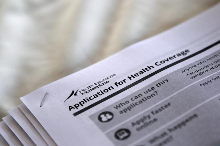The federal government forms for applying for health coverage are seen in this 2013 photo taken during a rally by supporters of the Affordable Care Act in Jackson, Miss. (CNS photo/Jonathan Bachman, Reuters)