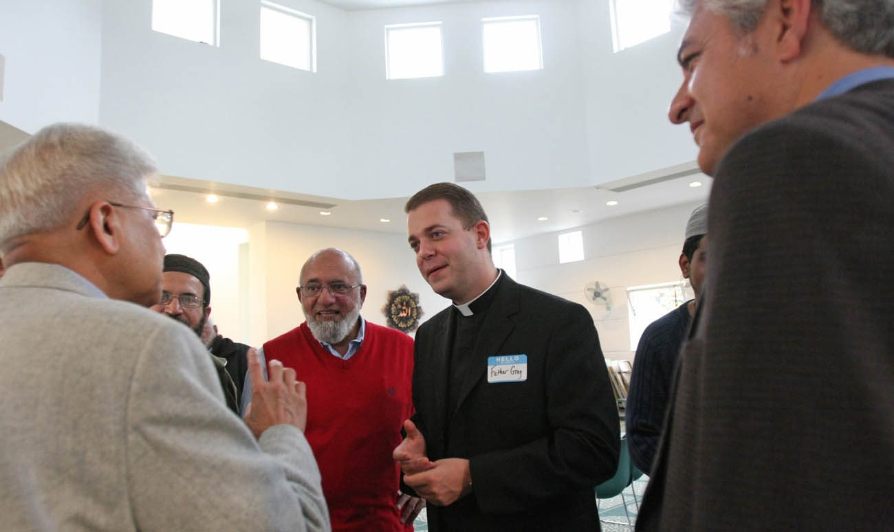 Father Gregory Rannazzisi chats with Muslim men during an open house in 2010 at the Islamic Center of Long Island in Westbury, N.Y. Father Rannazissi, a member of the ecumenical and interfaith commission of the Diocese of Rockville Centre, N.Y., is the diocese's liaison with Long Island's Muslim population. (CNS photo/Gregory A. Shemitz)
