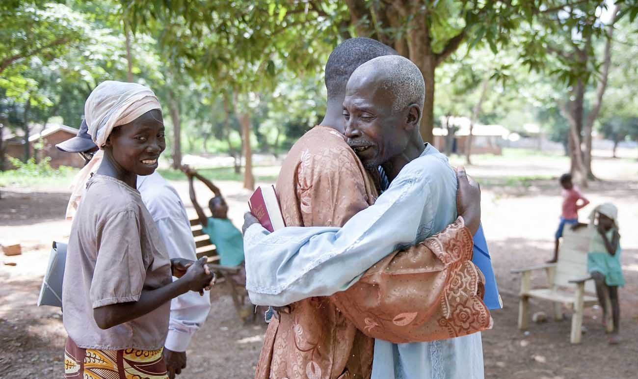 Villagers embrace in 2014 on the grounds of the Monastery of Boy Rabe in Bangui, Central African Republic. (CNS photo/Catianne Tijerina for Catholic Relief Services)
