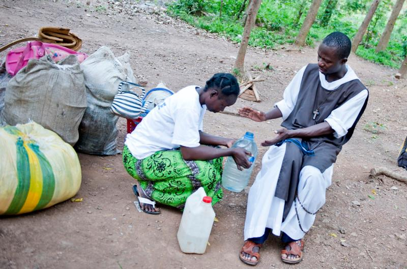 A clergyman blesses the water and prays over an internally displaced woman in 2014 at the Monastery of Boy Rabe in Bangui, Central African Republic. (CNS photo/Catianne Tijerina for Catholic Relief Services)