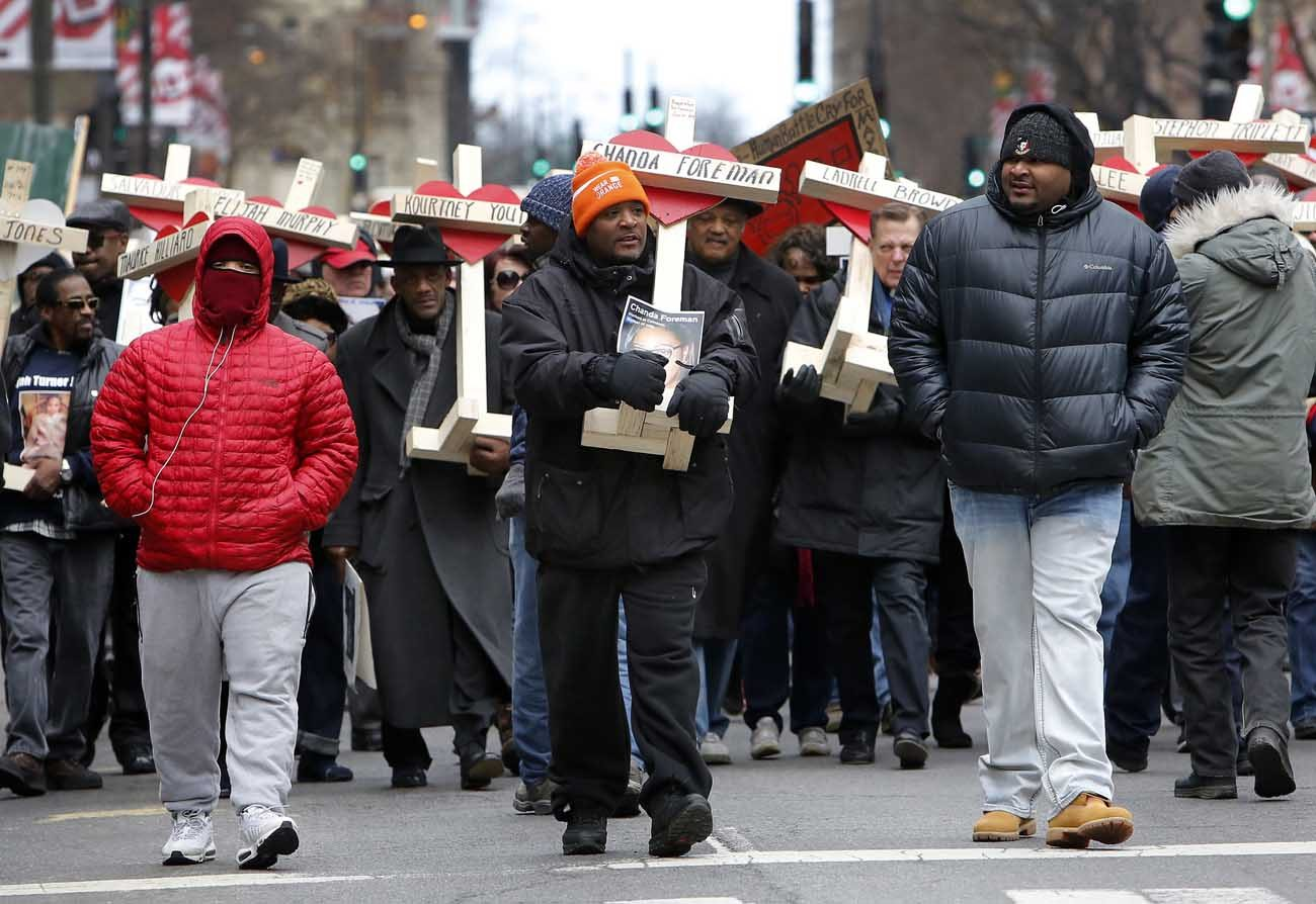 People carry crosses with names of victims of gun violence during a  Dec. 31 march in downtown Chicago. Hundreds of people joined the march organized by Father Michael Pfleger, pastor of St. Sabina Parish on the city's South Side, to remember those who died by gun violence in 2016. (CNS photo/Karen Callaway, Catholic New World)