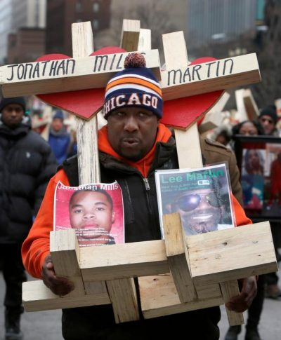 A man carries crosses with names of victims of gun violence during a Dec. 31 march in downtown Chicago. (CNS photo/Karen Callaway, Catholic New World)