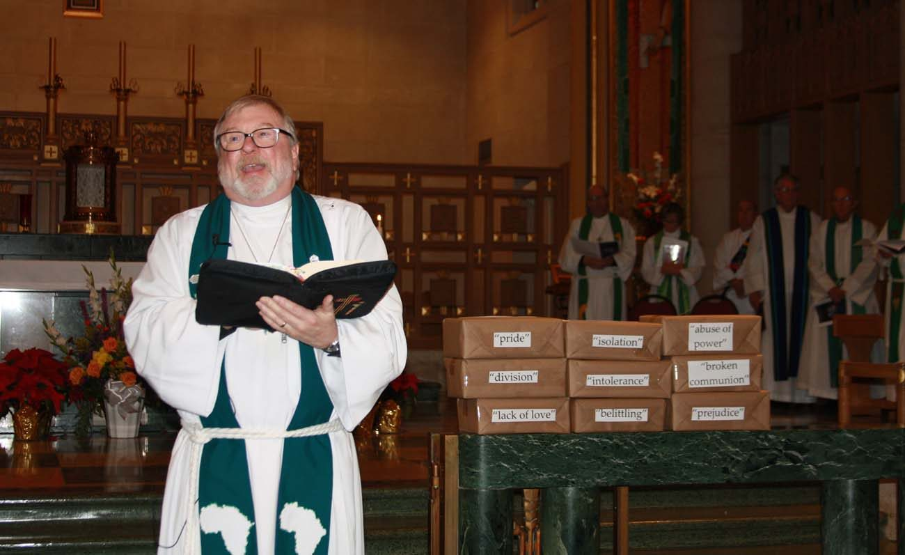 Bishop Rodger C. Prois, of the Western Iowa Synod of the Evangelical Lutheran Church in America, proclaims the Gospel reading at a Jan. 22 prayer service for Christian unity in Sioux City, Iowa. Next to Bishop Prois are boxes crafted to resemble stones that build a wall that have on them words that divide people of faith. (CNS photo/Joanne Fox, the Globe)