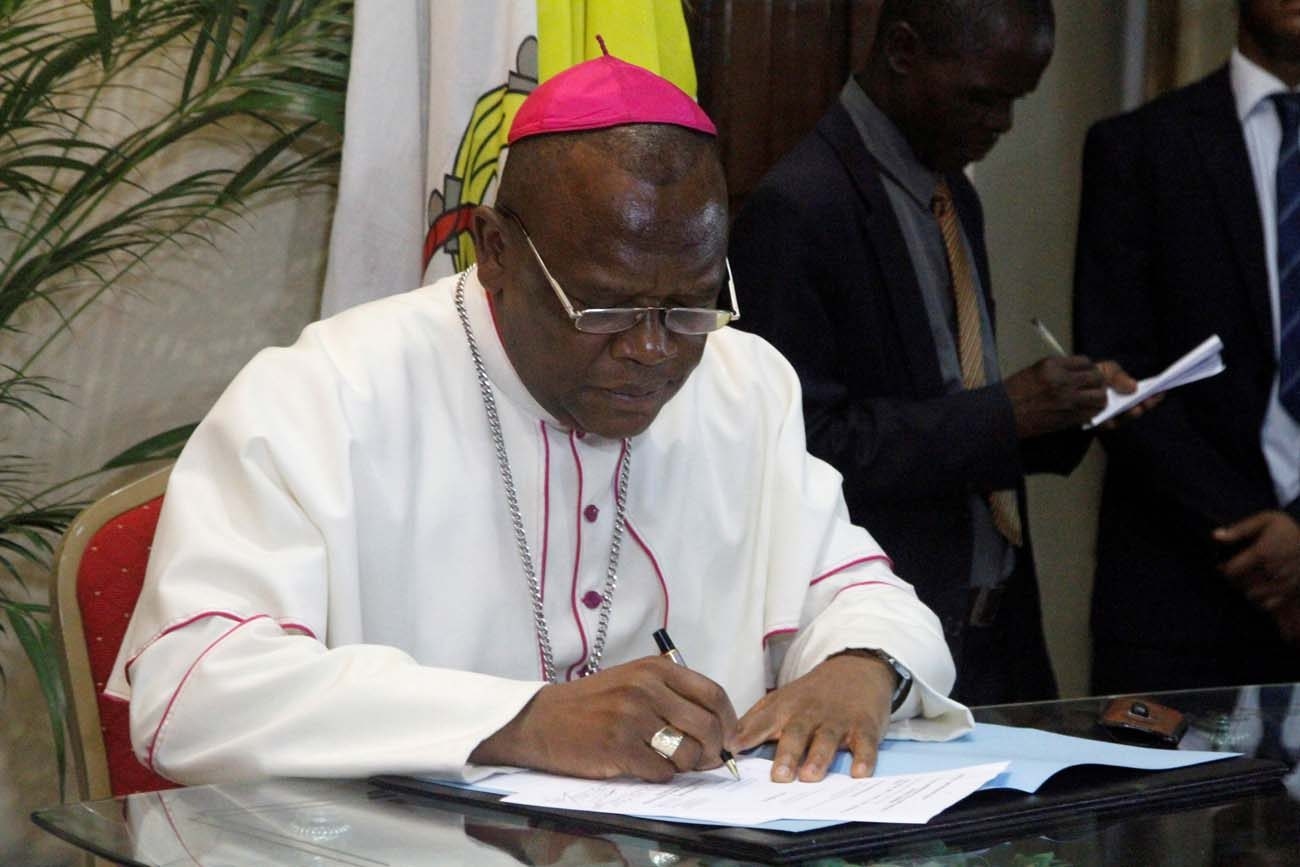 Congolese Bishop Fridolin Ambongo Besungu signs the accord between the opposition and the government of President Joseph Kabila Dec. 1 at the bishops' conference in Kinshasa. Kabila will step down as Congolese president after elections are held before the end of 2017, under an agreement by the government and the opposition. (CNS photo/Kenny Katombe, Reuters)