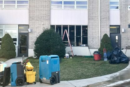 A rear view of SS. Colman-John Neumann School shows work in progress near the bolier room where the effects of an explosion were discovered in the early morning hours of Monday, Jan. 30. (Sarah Webb)
