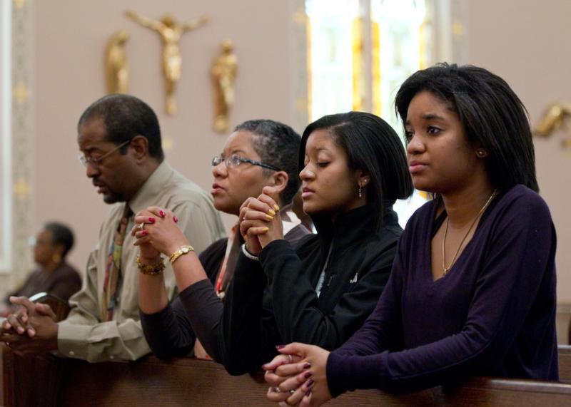 An African-American family prays after arriving for Mass in 2011 at St. Joseph's Catholic Church in Alexandria, Va. For the 29th year in a row, people of all faiths are urged to observe a national day of prayer for the African-American family Feb. 5 as part of Black History Month, observed every February. (CNS photo/Nancy Phelan Wiechec)