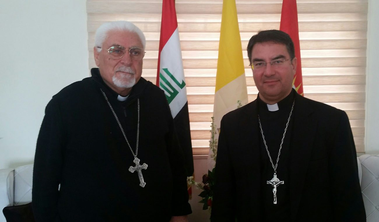 Syriac Catholic Archbishop Yohanna Moshe of Mosul, Iraq, and Bishop Oscar Cantu of Las Cruces, N.M., pose for a photo in Iraq. After meeting with church leaders in northern Iraq, Bishop Cantu said he will advocate differently for Iraqi religious minorities. (CNS photo/Stephen Colecchi, USCCB)