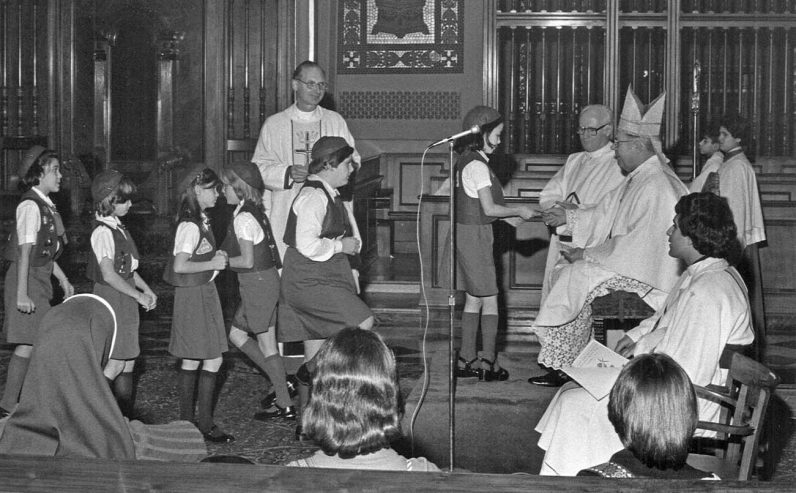 Bishop Lohmuller gives religion awards to Agape Camp Fire girls Dec. 3, 1977 at the Cathedral Basilica of SS. Peter and Paul. (Robert and Theresa Halvey Photograph Collection)
