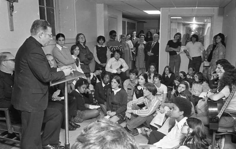 Bishop Martin N. Lohmuller speaks with young people in October 1973 during the blessing of the new headquarters for the archdiocesan CYO (Catholic Youth Organization) on Clover Street in Philadelphia. (Robert and Theresa Halvey Photograph Collection)