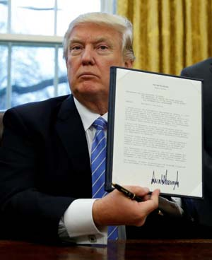 "U.S. President Donald J. Trump holds up his executive order reinstating the ""Mexico City Policy"" banning federal funding of abortion-providing groups abroad after he signed it Jan. 23 in the Oval Office of the White House in Washington. (CNS photo/Kevin Lamarque, Reuters)"