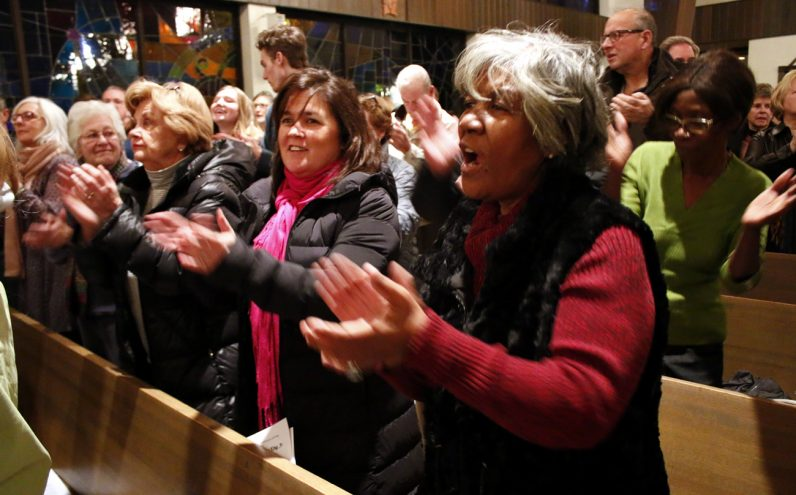 Kim McCabe from St. Genevieve Parish in Flourtown and Rosalyn Butts from St. Barbara Parish in West Philadelphia sing praise together after meeting for the first time.