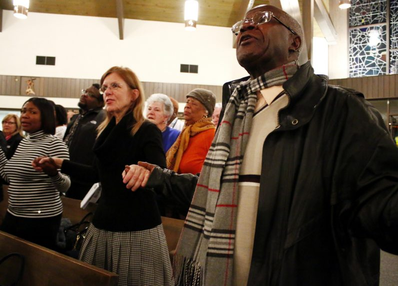 """Sandra Mollichella (left) and Gesner Brutus hold hands as they sing """"We Shall Overcome."""""""