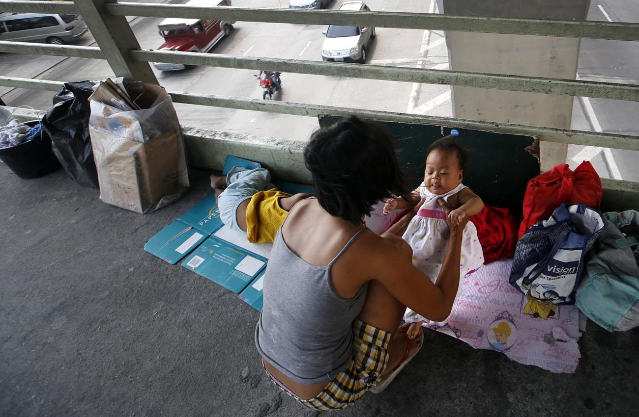 A mother holds her daughter in 2014 on a footbridge in Manila, Philippines. The Philippine president's executive order that the government begin distributing free contraceptives to the poor by 2018 may face delays because of a pending case before the country's Supreme Court. (CNS photo/Ritchie B. Tongo, EPA)