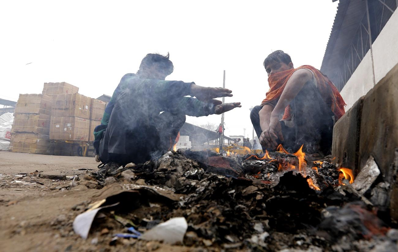 "Young homeless Indian men warm themselves near a fire during a cold winter morning in 2016 in New Delhi. ""In these very cold days, I think and I invite you to think of the people who live on the streets, struck by the cold and, many times, by indifference,"" Pope Francis told people in St. Peter's Square Jan. 8. (CNS photo/Rajat Gupta, EPA)"