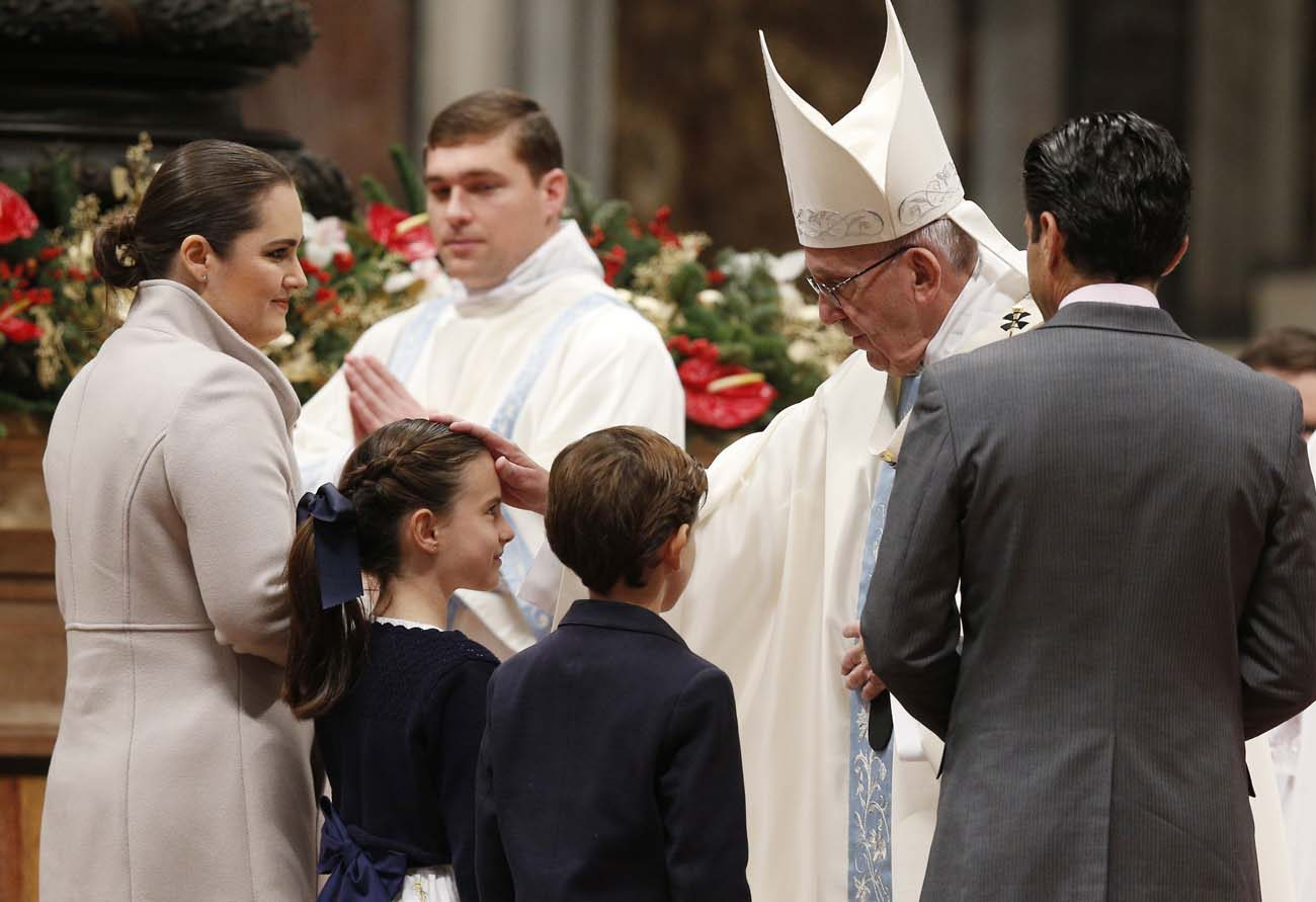 Pope Francis greets a family as they present offertory gifts during a Mass marking the feast of Mary, Mother of God, in St. Peter's Basilica at the Vatican Jan. 1. (CNS photo/Paul Haring)