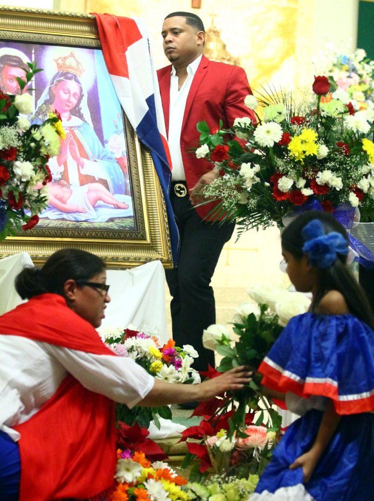 Flowers are placed before the image of Virgen de la Altagracia.