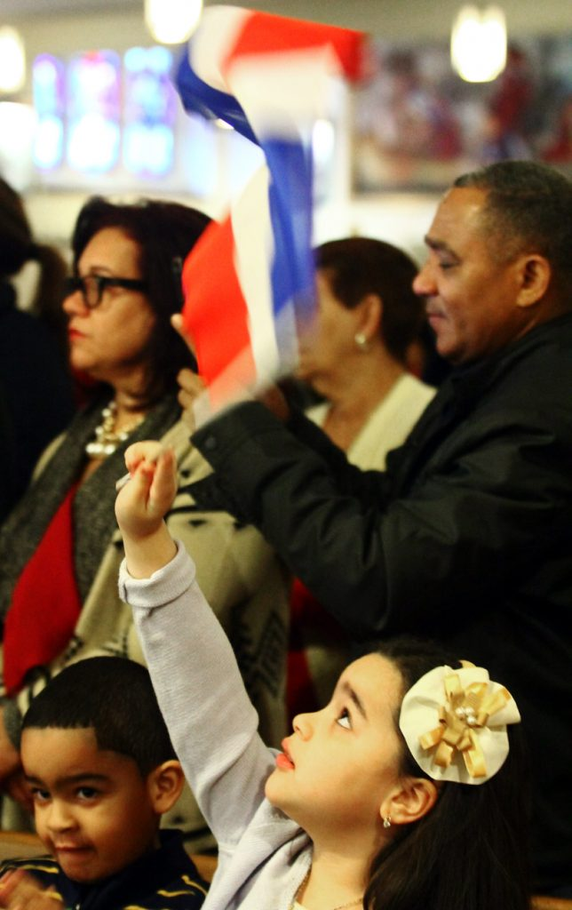 Noelia Valdez enjoys waving her flag during the entrance procession for Mass.