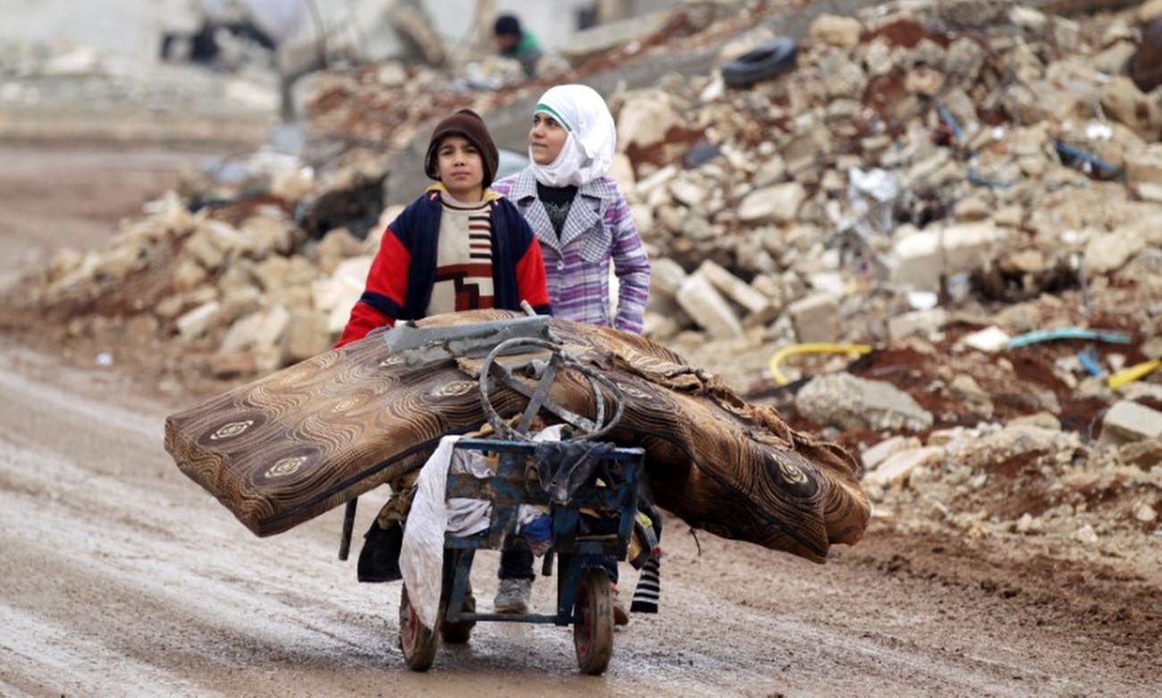 Syrian children transport their salvaged belongings from their damaged house in Doudyan, a village in northern Aleppo Jan. 2. (CNS photo/Khalil Ashawi, Reuters)