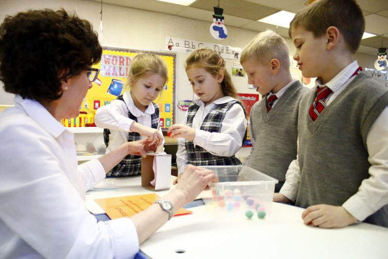 Kindergarden students learn about digestion by putting cotton balls into a tube leading to a balloon.