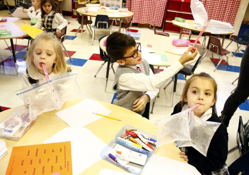 Kindergarten students show off the lung models they built, consisting of sealed plastic bags and straws.