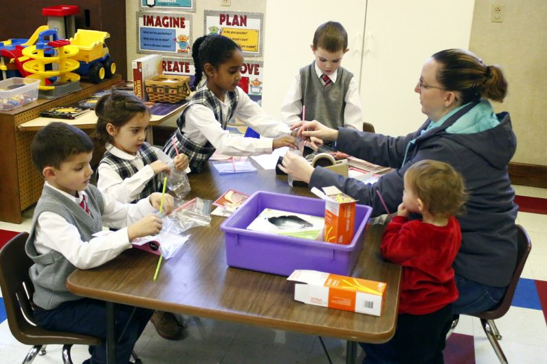 Kindergarten students build models of lungs with the help of a parent volunteer.