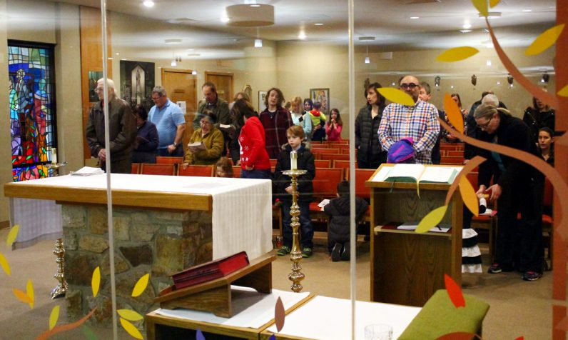 The overflow of people attending Mass are able to participate from the adjoining chapel.