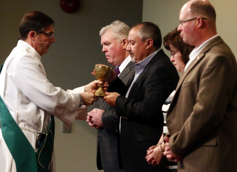 Deacon Tim Lynch distribues the blood of Christ to extraordinary ministers of holy Communion.