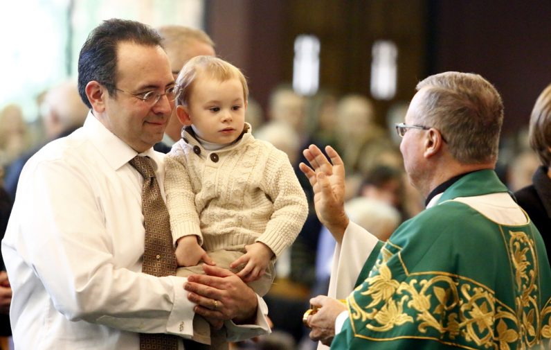 Msgr. Francis Beach blesses a child before giving his father holy Communion.