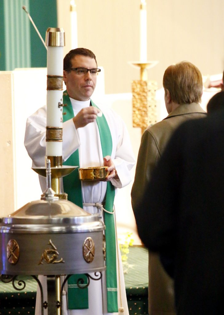 Father Jeff Rott distribues holy Communion.
