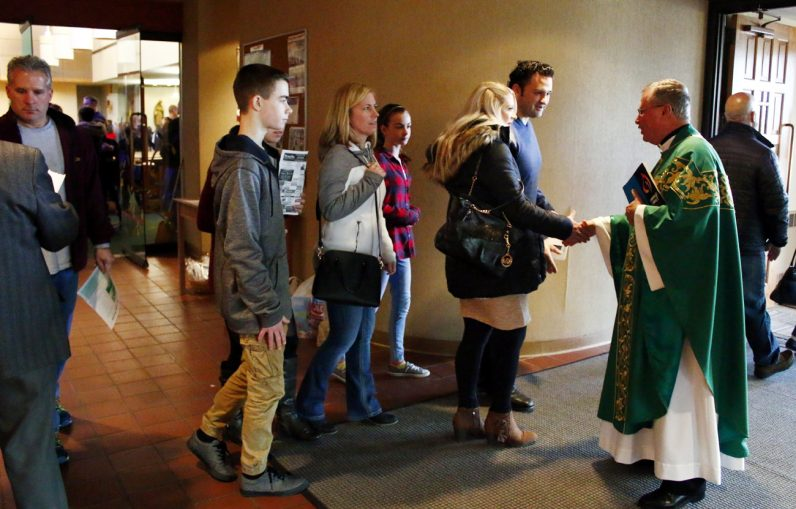 Msgr. Francis Beach greets parishioners after Mass.