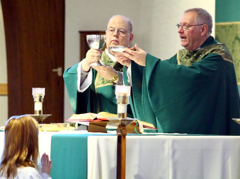 Deacon George Morris (left) assists at the altar with Msgr. James D. Beisel, celebrant for the Mass.