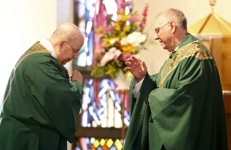 Deacon George Morris receives a blessing from Msgr. James D. Beisel before proclaiming the Gospel.