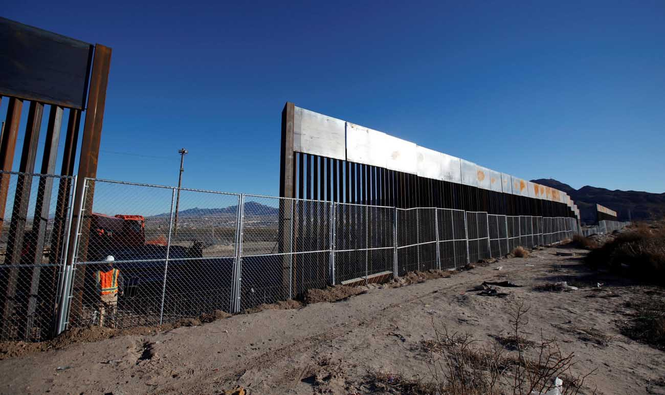 A worker stands next to a newly built section of the U.S.-Mexico border wall in 2016 at Sunland Park, U.S. opposite the Mexican border city of Ciudad Juarez, Mexico. President Donald Trump enacted two executive memorandums to deal with security, including one that calls for construction of a wall along the U.S.-Mexico border. (CNS photo/Jose Luis Gonzalez, Reuters)